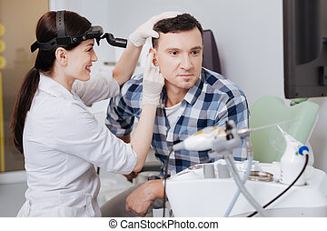 Happy young doctor examining ear of her friend