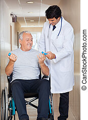 Happy young doctor giving hand weights to the senior man sitting in a wheelchair at hospital