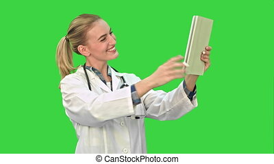 Happy young doctor naving video conference on tablet with patient on a Green Screen, Chroma Key.