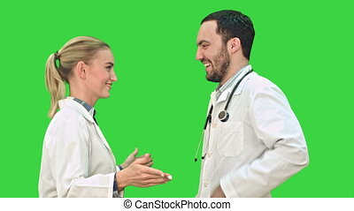 Happy young doctors wearing white medical overall dancing on a Green Screen, Chroma Key.
