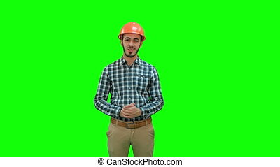 Happy young engineer in helmet talking to the camera on a Green Screen, Chroma Key.