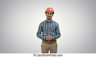 Happy young engineer in helmet talking to the camera on white background.