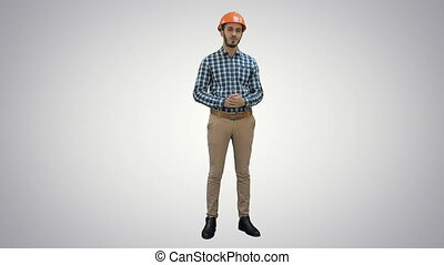 Happy young engineer wearing helmet talking to the camera on white background.