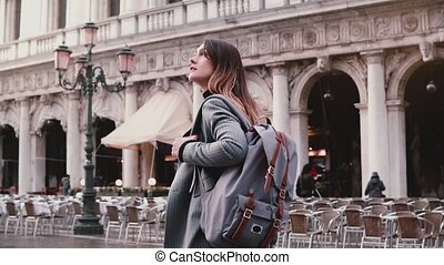 Happy young European businesswoman tourist enjoying walking along beautiful old San Marco city square in Venice, Italy.
