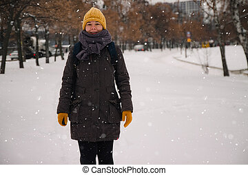 Happy young european woman in a yellow knitted hat and mittens with a backpack, laughs under the snowfall. Retro effect. Blur