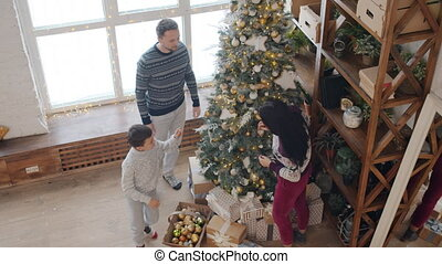 Happy young family decorating New Year tree in cozy house talking having fun