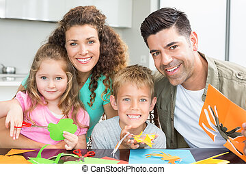 Happy young family doing arts and crafts at the table