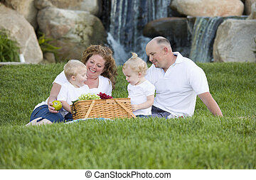 Happy Young Family Enjoy Picnic in Park