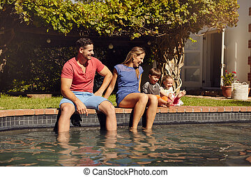 Happy young family enjoying near pool