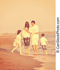 happy young family have fun on beach at sunset