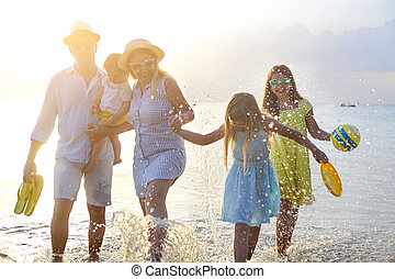 Happy young family have fun on beach run and jump