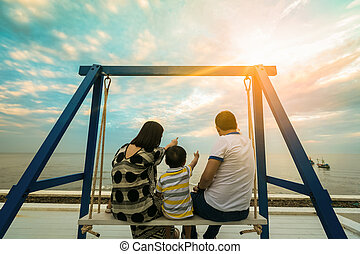 Happy young family have fun sitting swing on beach at sunset.