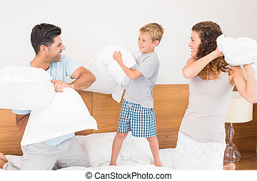 Happy young family having a pillow fight