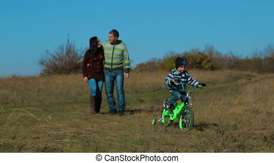 Happy Young Family Having A Promenade In Autumn Meadow