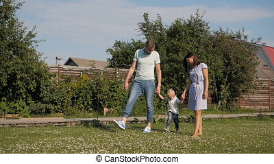 Happy Young Family Having Fun Outdoors. Mom, Dad and Kid Walking, Enjoying Nature Outside.