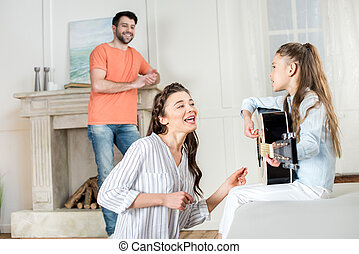 Happy young family having fun with guitar at home