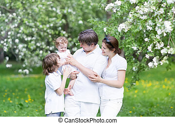 Happy young family in a blooming apple tree garden