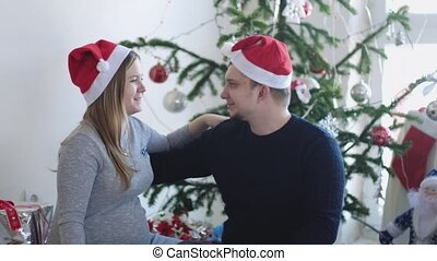 Happy young family in Santa cap. Husband hugs him pregnant wife near beautiful decorated Christmas tree. slow motion. 3840x2160