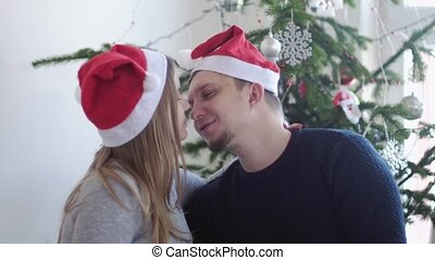 Happy young family in Santa cap. Husband kiss him pregnant wife near beautiful decorated Christmas tree. slwo motion. 3840x2160
