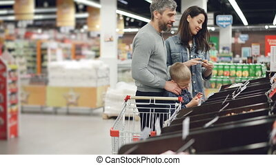 Happy young family is shopping in supermarket, mother is checking food in containers, father is talking to his happy laughing son. Shelves with products are visible.