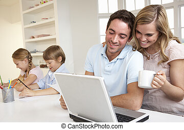 Happy young family looking and reading a laptop computer