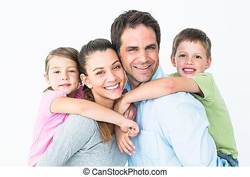 Happy young family looking at camera together on white ...