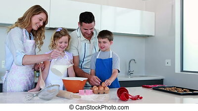 Happy young family making a cake to