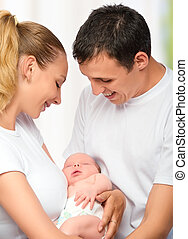 happy young family of mother, father and newborn baby in their arms to embrace
