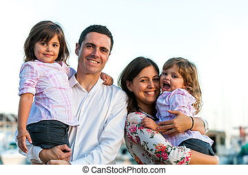 Close up portrait of young couple with their two little daughters outdoors in late afternoon sun.