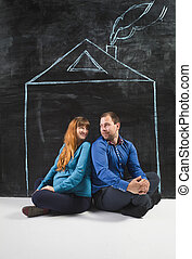 happy young family posing in house drawn on chalkboard