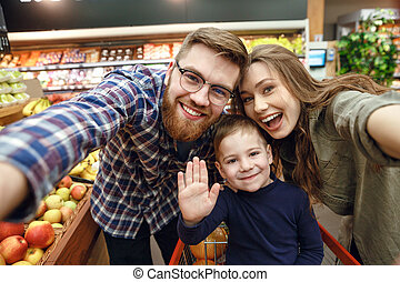 Happy young family posing in supermarket and looking at the...