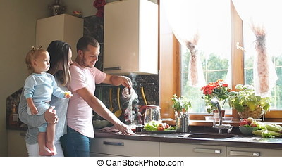 Happy young family preparing breakfast in the kitchen. Slow motion