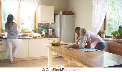 Happy young family preparing breakfast in the kitchen.
