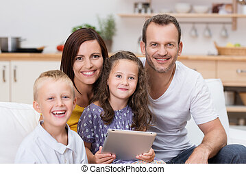 Happy young family relaxing with a tablet-pc
