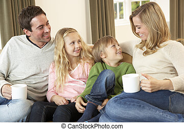 Happy young family sitting and talking on sofa
