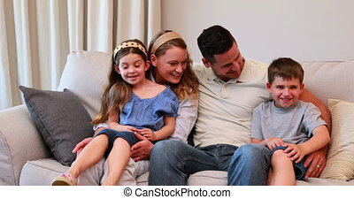 Happy young family sitting on sofa smiling at camera at home in the living room