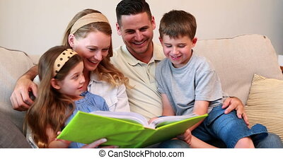 Happy young family sitting on sofa looking at photo album at...
