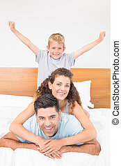 Happy young family smiling at camera on bed posing