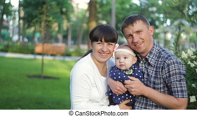 Happy young family spending time together outside in green summer park