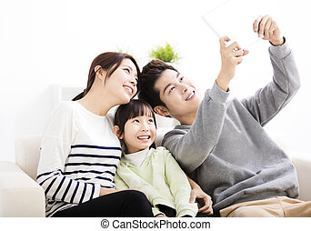 Happy young family taking selfies on sofa