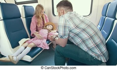Happy young family traveling together - talking in the train and look out the window