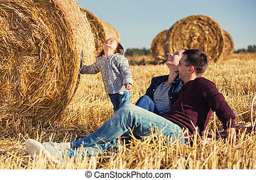 Happy young family with 2 year old girl next to hay bales in...