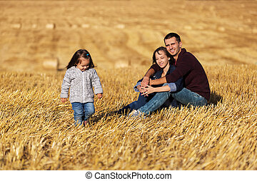 Happy young family with 2 year old girl sitting on the ground in harvested field