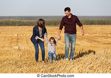 Happy young family with 2 year old girl walking in a harvested field