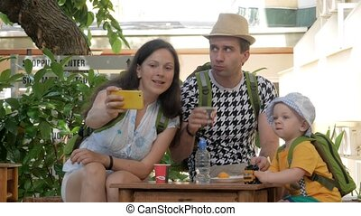 Happy young family with a baby eating on the open air in a cafe. Everyone is sitting on small wooden chairs