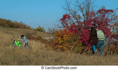 Happy Young Family With a Child On Bike Walking In Autumn Meadow