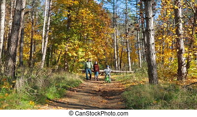 Happy Young Family With a Child On Bike Walking Along Footpath In Autumn Park