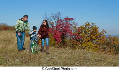 Happy Young Family With a Child Walking In Autumn Meadow