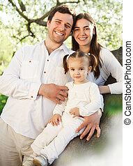 Happy young family with baby girl outdoors