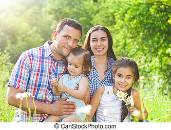 Happy young family with children in the spring forest
